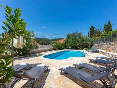 Swimming pool of the villa Mir Vami in Sumartin, surrounded by greenery and loungers.