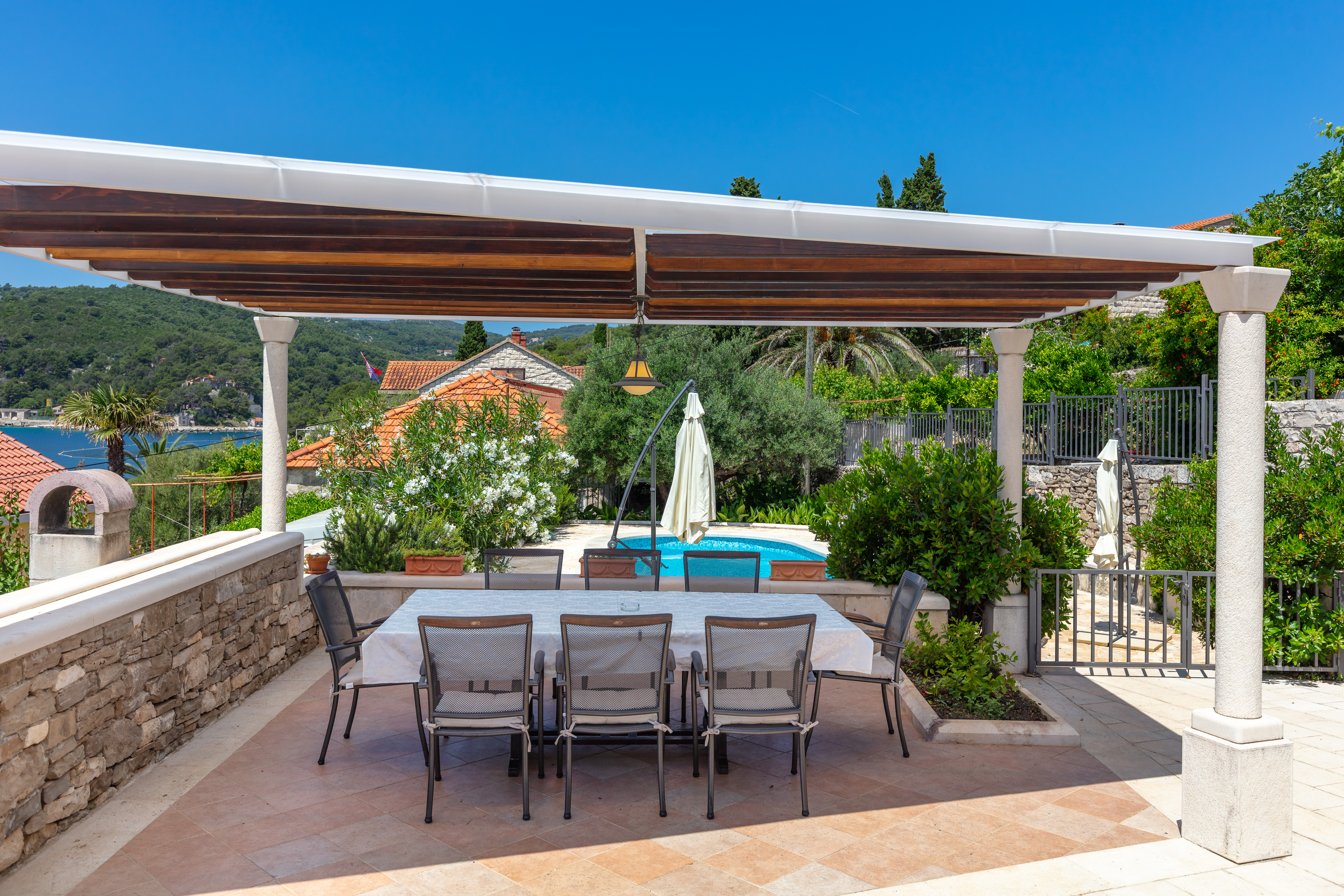Covered outside dining area with swimming pool view