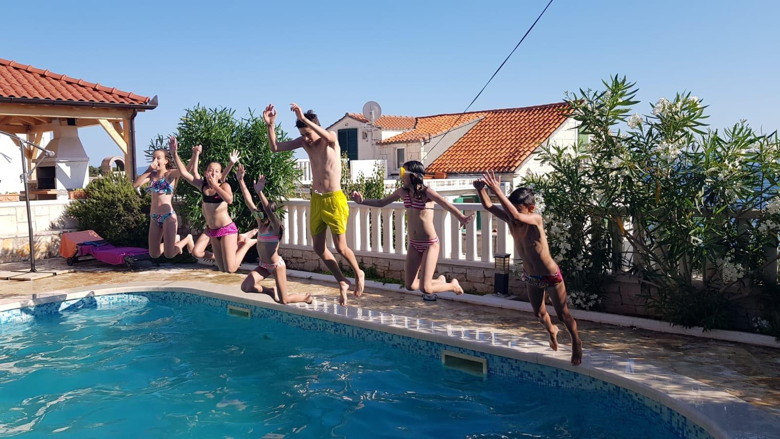 Children jumping into the swimming pool of the Villa Mir Vami in Sumartin in Croatia